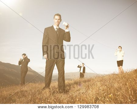 Business people communicate through the paper cup phone outdoors.
