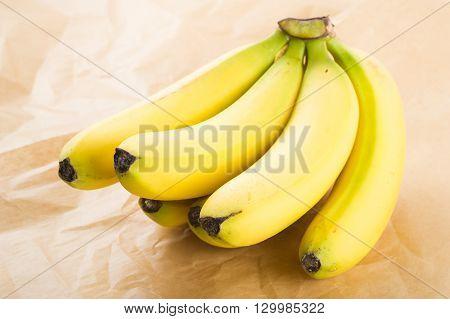 Fresh organic bananas on brown paper as background