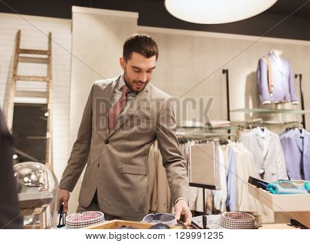 sale, shopping, fashion, style and people concept - happy elegant young man or businessman in suit choosing shirt in mall or clothing store