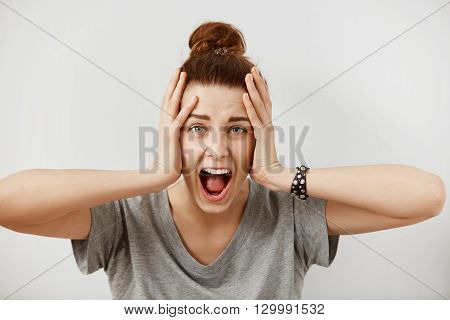 Young Woman Screaming In Terror With Hands On Her Head, Mouth Wide Open Looking In Panic At The Came