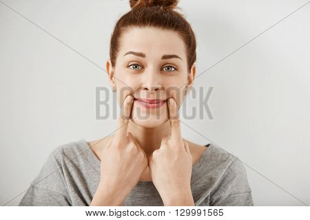 Headshot Of Young Caucasian Woman Making Fake Smile With Her Fingers Stretching The Corners Of Her M