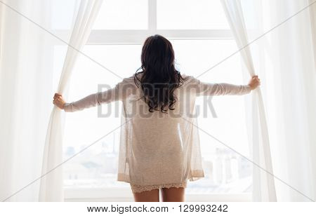 people and morning concept - close up of happy woman opening window curtains at home