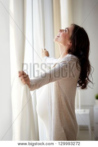 pregnancy, motherhood, people and expectation concept - happy pregnant woman opening window curtains at home