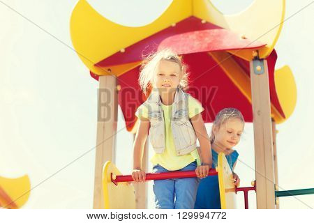 summer, childhood, leisure, friendship and people concept - happy kids on children playground climbing frame