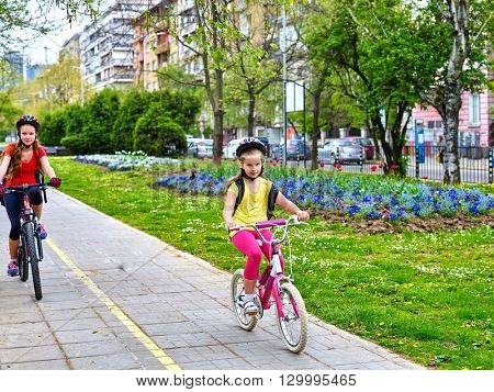 Bikes bicyclist girl. Girls wearing bicycle helmet  with rucksack ciclyng bicycle. Girls children cycling on yellow bike lane. Bike share program save money and time. Children outrace one another.