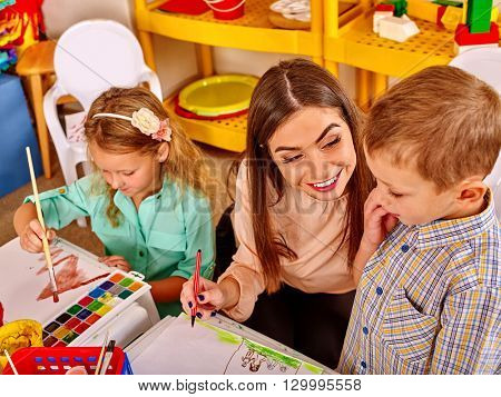 Children with teacher woman painting on paper at table  in  kindergarten . Learning children in start school.