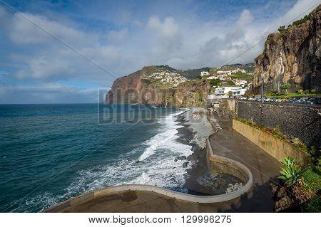 Long Madeiran embankment view and villages on the mountains. Rocky shores of Madeira island south coast. Walking route near Camara de Lobos town.