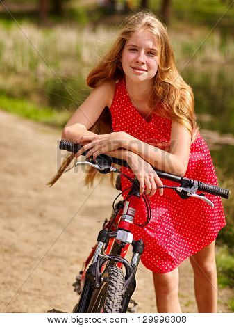 Bikes cycling girl. Girl with long blond hair wearing red polka dots dress rides bicycle into park. Girl in ecotourism. Cycling is good for health. Cyclist is unrecognizable.