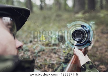 hunting, war, army, technology and people concept - close up of young soldier or sniper holding gun with virtual screen projection and aiming in forest