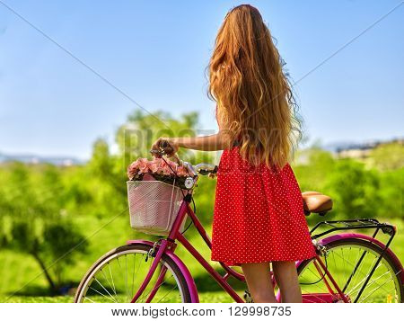 Bikes bicycle girl. Girl with long blond hair wearing red polka dots dress looking into distance keeps bicycle with flowers basket.  Green grass. Back view.