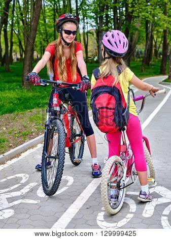 Bikes bicyclist girl. Two girls wearing bicycle helmet and glass with rucksack ciclyng bicycle. Girls children cycling meet on white bike lane. Bike share program save money and time at city street.
