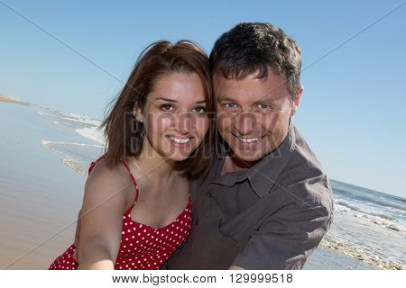 Happy Couple Cuddling At The Beach By The Sea