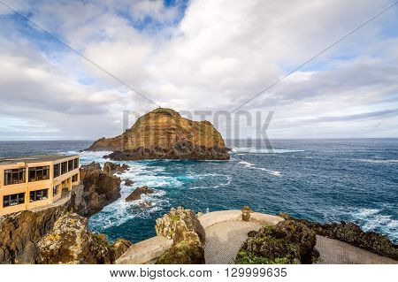 Volcanic lava creations and rock with a lighthouse in the ocean. Porto Moniz embankment, Madeira island, Portugal.
