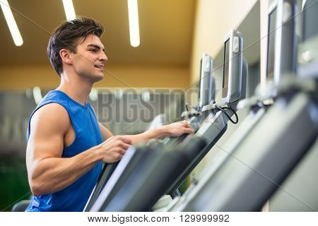 Young man at elliptical indoors