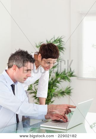 Portrait of a man pointing at something to his colleague on a notebook in an office