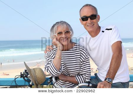 Senior couple riding bikes by the beach