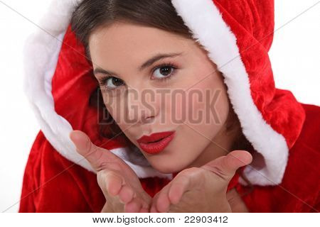 Woman dressed as Santa blowing a kiss to camera