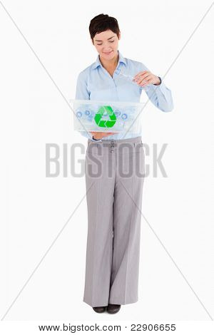 Woman putting an empty plastic bottle in a recycling box against a white background