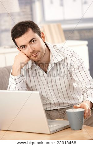 Young male working at home, sitting on sofa, using laptop.?