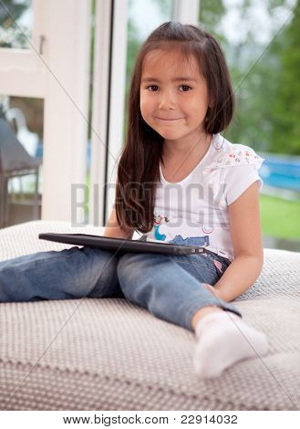 Portrait of a cute young child at home using a digital tablet, looking at the camera