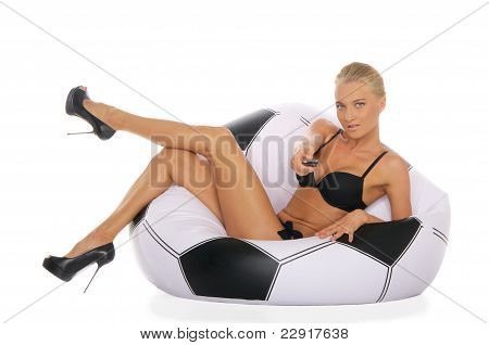 Woman with remote control in chair of soccer ball