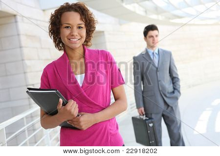 A handsome african business woman with co-worker in background