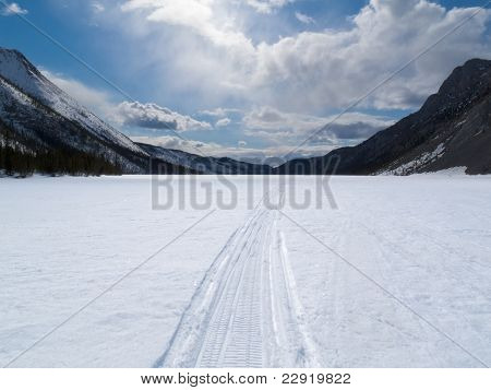 Well used winter trail on frozen mountain lake