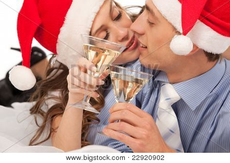 Young lovely couple in Santa hats holding the glasses of champagne and clinking glasses. Isolated over white background. (Focus is on champagne glasses)