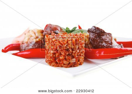 rice with roast meat chunks and pepper on white  plate isolated over white background