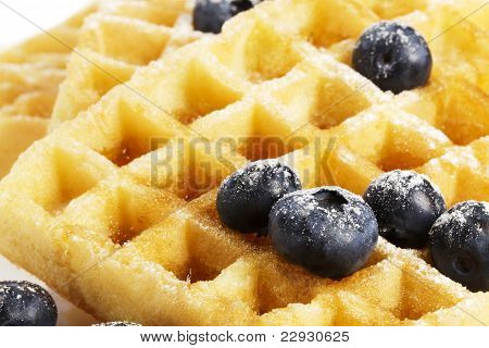 closeup from waffels with sugar covered blueberries and syrup