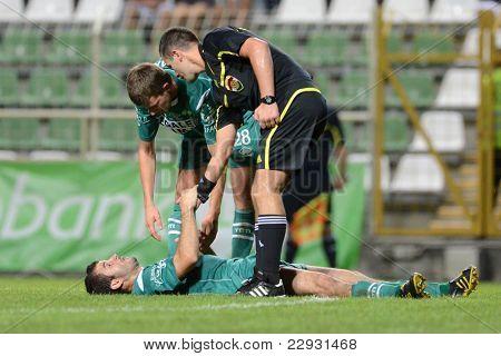KAPOSVAR, HUNGARY - AUGUST 27: Pedro Sass (green 33) injured at a Hungarian National Championship soccer game - Kaposvar (green) vs Paks (white) on August 27, 2011 in Kaposvar, Hungary.
