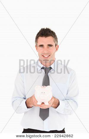Portrait Of A Businessman Showing A Piggy Bank