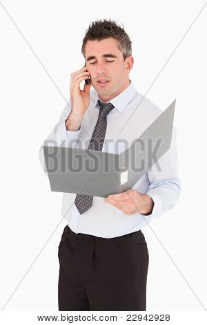 Portrait Of A Businessman Making A Phone Call While Holding A Bi
