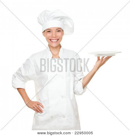 Chef showing empty plate. Happy smiling portrait of female in chef uniform and chef hat isolated on white background. Asian Caucasian woman model.