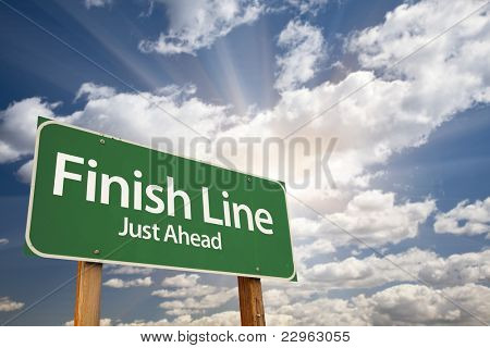 Finish Line, Just Ahead Green Road Sign Over Dramatic Sky, Clouds and Sunburst.