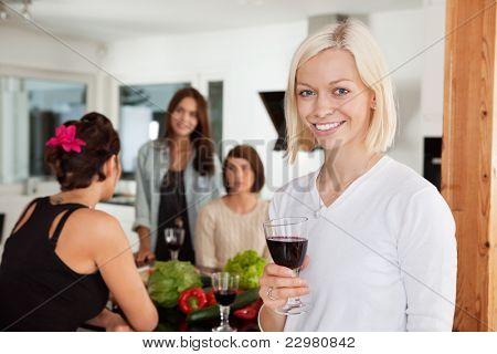 Sonriente con vidrio en fiesta con amigas en fondo