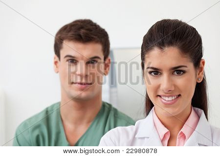 Portrait of pretty female doctor smiling with colleague standing behind
