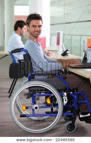 Young man in a wheelchair using a computer in the workplace