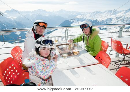 Winter, ski - family enjoying lunch in winter mountains