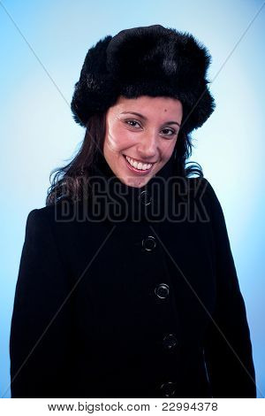 Beautiful Woman Smiling, With A Cap And A Coat, Isolated On Blue Background. Studio Shot.