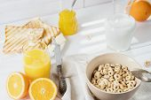 Delicious Healthy Breakfast.  Whole Grain Cereal Rings, Milk, Honey And Orange Juice On The White Ta poster