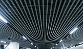 Lights And Ventilation System In Long Line On Ceiling Of The Dark Office Industrial Building Exhibit poster