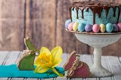 Blue Frosted Cake With Chocolate Drip Frosting And Easter Eggs In A Rustic Setting poster