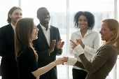 Funny Smiling Businesswomen Holding Hands Celebrating Success While Diverse Team Applauding, Female  poster