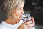 Senior Woman In The Kitchen. An Old Woman Inside The House, Drinking Water. Close Up. poster