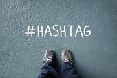Social network hashtag on floor with man standing looking down concept for trending, marketing and m poster