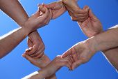 picture of fellowship  - Various peoples hands in front of bright blue sky - JPG