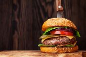 Tasty grilled home made burger with beef, tomato, cheese, cucumber and lettuce. With space for your  poster