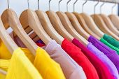 Fashion clothes hanging on clothing rack - bright colorful selection of clothes closet. Rainbow colo poster