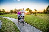 Beautiful young family jogging together outdoors along a pathway at a city park. poster
